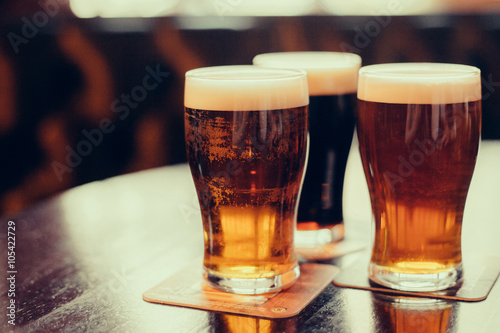 Photo sur Aluminium Biere, Cidre Glasses of light and dark beer on a pub background.