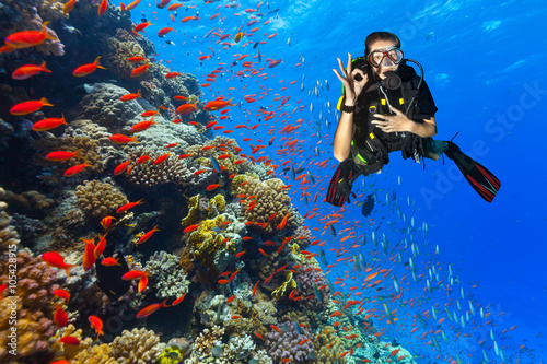 Fotobehang Duiken Scuba diver explore a coral reef showing ok sign