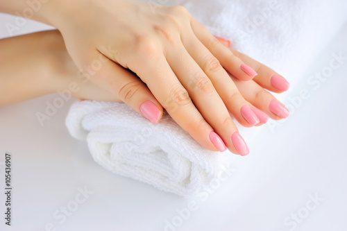 Photo sur Aluminium Manicure Hands of a woman with pink manicure are on a towel