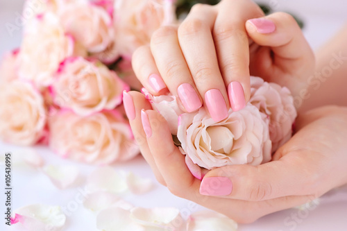 Obraz na płótnie Hands of a woman with pink manicure on nails  and roses
