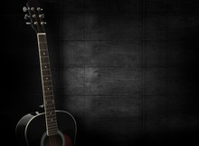 Black Acoustic Guitar On Dark Black Wooden Background.