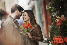 A Man And Woman By A Flower Stall In The City, Holding A Bunch Of Bright Red Flowers,
