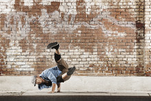 A Young Man Doing A Breakdance Move Balancing On His Hands On The Street Of A City,