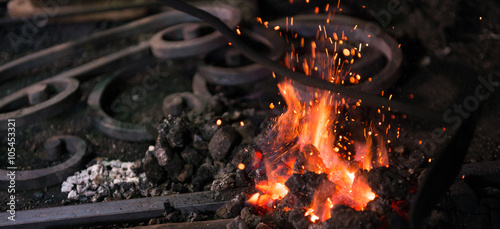 Fotografia Ironworker forging hot iron in workshop