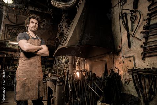 Valokuvatapetti Ironworker forging hot iron in workshop