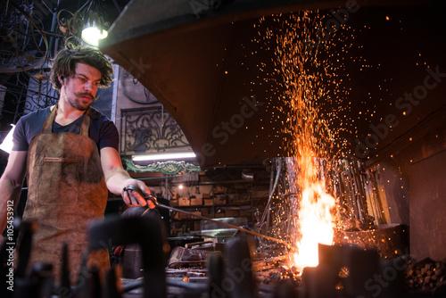 Ironworker forging hot iron in workshop Canvas-taulu