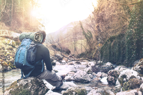Obraz hiker man crossing the river to reach the other side - fototapety do salonu