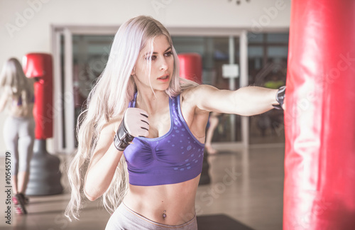obraz PCV Woman fighter hit the heavy boxing bag