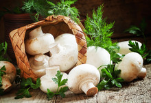 White Mushrooms Spill Out Of A Wicker Basket On An Old Wooden Ba