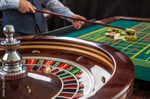 фотография  Roulette and piles of gambling chips on a green table.