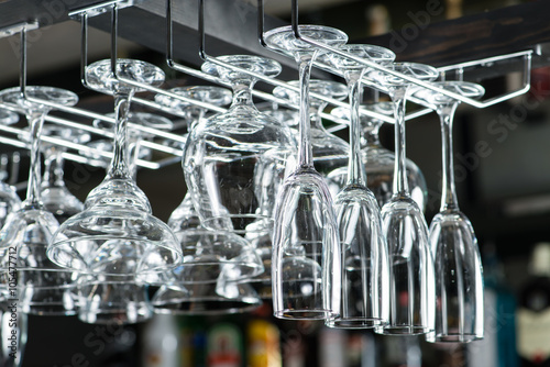 Close up on bar with wine glasses hanging above it at the nightc