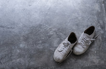 A Pair Of Old Dirty Shoes On The Cement Floor With Light Shading From The Corner.