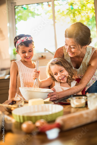 Foto op Plexiglas Koken A mother is cooking a cake with her two young daughters