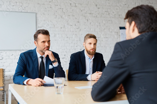 Obraz Job interview - two business man recruit candidate at their office - fototapety do salonu