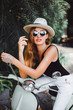 young girl with long hair in sunglasses in a black t-shirt tattoo on his shoulder in white pants with red lipstick posing on a retro scooter Vespa colors taifani vintage style straw hat with a stylish