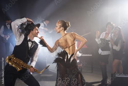 Girl dancing with saxophonist Fototapeta