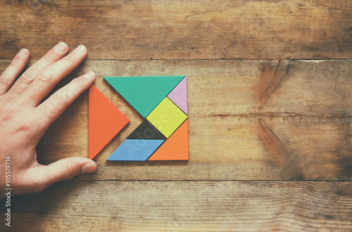 Fotografía  man's hand holding a missing piece in a square tangram puzzle, over wooden table