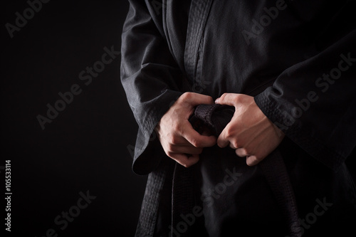 Photo Stands Martial arts Closeup of male karate fighter hands on the knot of black belt