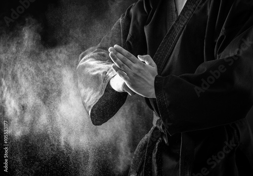 Photo Stands Martial arts Closeup of male karate fighter hands. Black and white.