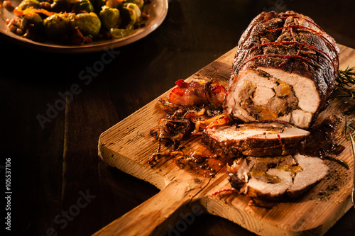 Fotografía  Roasted pork sliced with bacon on cutting board