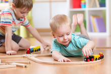 Little Boys Playing With Wooden Train Set