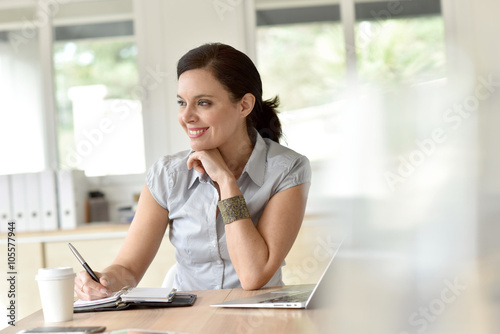 Fototapety, obrazy: Businesswoman in meeting room writing on agenda