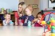 canvas print picture - Erzieherin am Tisch Kinder trinken aus Trinkflasche mit Spielzeug
