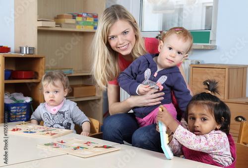 Fotografie, Obraz  Erzieherin am Tisch mit Kinder beim Puzzeln