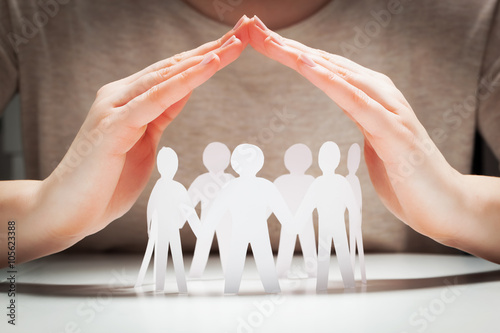 Fotografia  Paper people under hands in gesture of protection