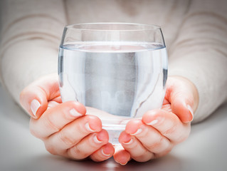 Naklejka A glass of clean mineral water in woman's hands. Environment protection, healthy drink.