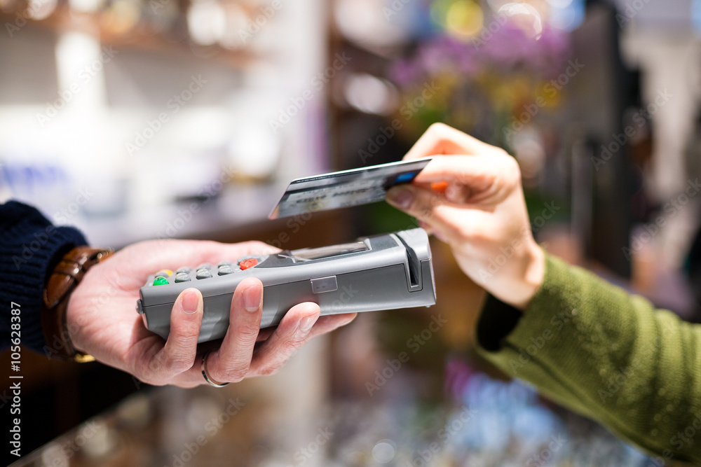 Fototapeta Woman paying with NFC technology on credit card