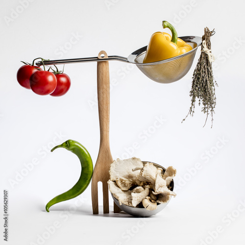 concept of sophisticated gastronomy with gourmet food ingredients playing with cuisine utensils for fun health and vegetable design on white background