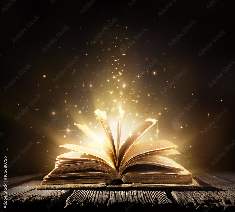 Old Book With Magic Lights On Vintage Table