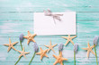 Marine items, flowers and empty tag on wooden background.