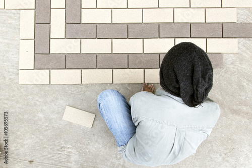 Photo  construction mason man hands on tiles work with notched trowel cement mortar