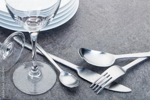 Fotografia  Glänzende Gabel, Teelöffel, Löffel und Messer aus Edelstahl und Gläser angeordne