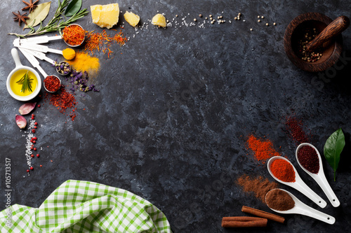 Fotografering  Herbs and spices over black stone