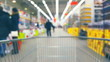 Supermarket interior with customers and trolley, blurred background