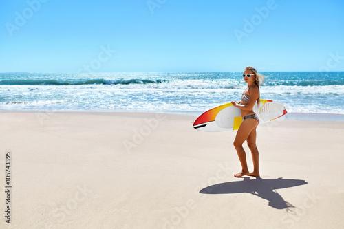 Plakat Sporty wodne. Surfing. Zdrowy szczęśliwy seksowny pasuje surfer kobieta, dziewczyna w bikini zabawy z deska surfingowa na plaży. Wakacje letnie. Styl życia. Czas wolny Aktywność sportowa. Letni relaks