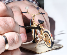Miniature Of Wooden Bicycle On White Background. Handcrafting Process, Craftsman's Hand Holding The Tool. Macro Shot.