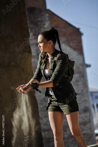 фотография  Girl near the brick wall in military style. Lara Croft style.