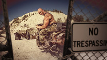 Muscular Bald Biker On The Desert Background.