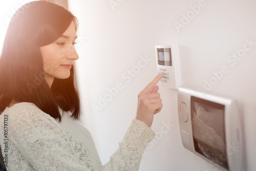 woman entering code on keypad of home security alarm Canvas Print