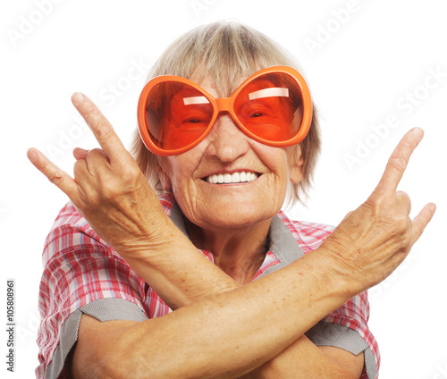 Fotografia  Senior woman wearing big sunglasses doing funky action isolated