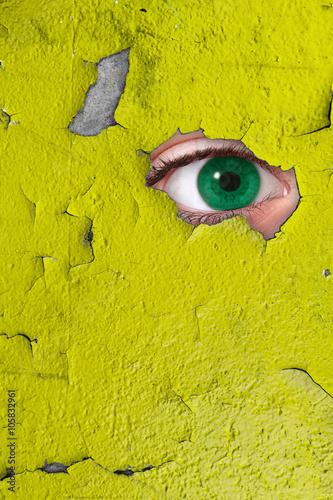 Fotografía  occhio che spia attraverso un buco nel muro