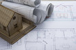 Real Estate concept. Architect workplace. Architectural project, blueprints, blueprint rolls and model house on plans. Top view. Construction background. Engineering tools.