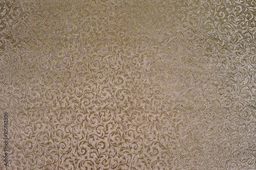 Fotografía  Texture of golden satin fabric with floral embossing.