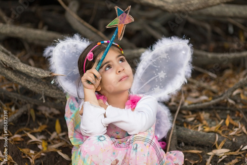 Fotografie, Obraz  Portrait of a cute little girl dressed up as a fairy sitting in a forest and pla