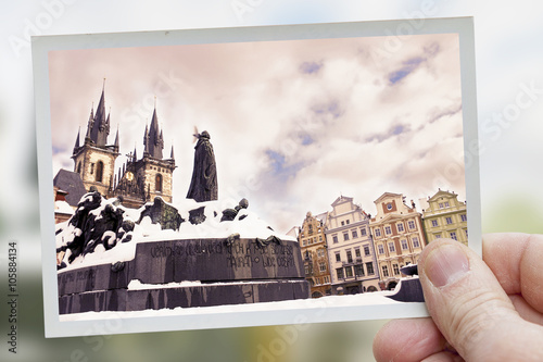 Cuadros en Lienzo hand holds snapshot of tyn square in prague on blurred backgroun