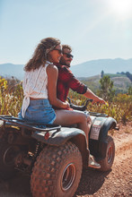 Young Couple Enjoying A Quad Bike Ride In Countryside